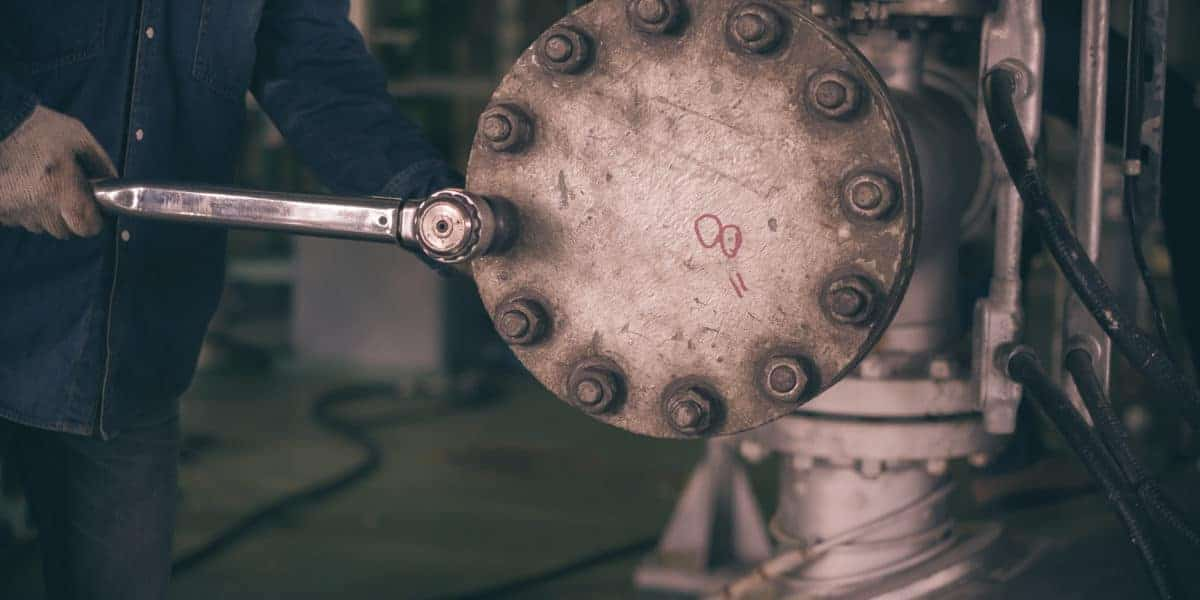 A manual torque wrench being applied in an industrial setting.